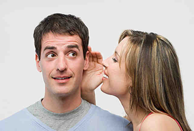 Woman whispering to man