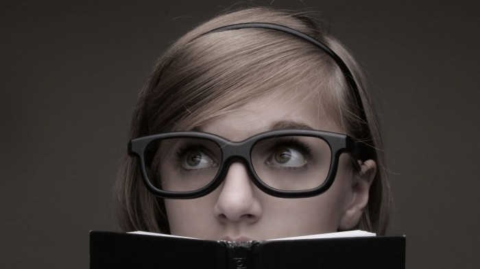nerdy-girl-looking-over-a-book-700x393