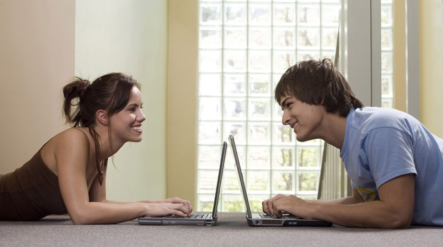 Teenage girl and a young man using laptops