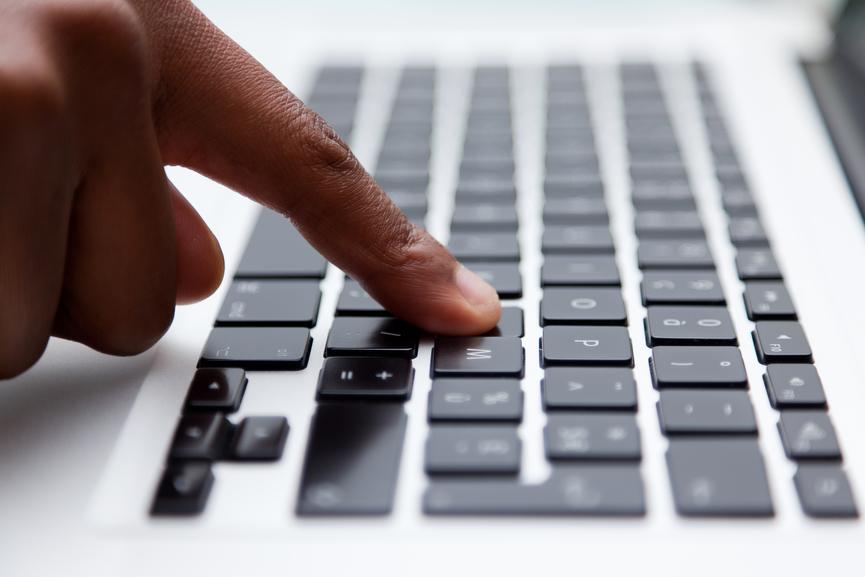 Black finger typing on computer keyboard