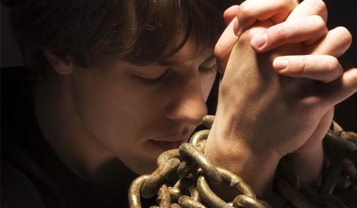 Man in chains praying